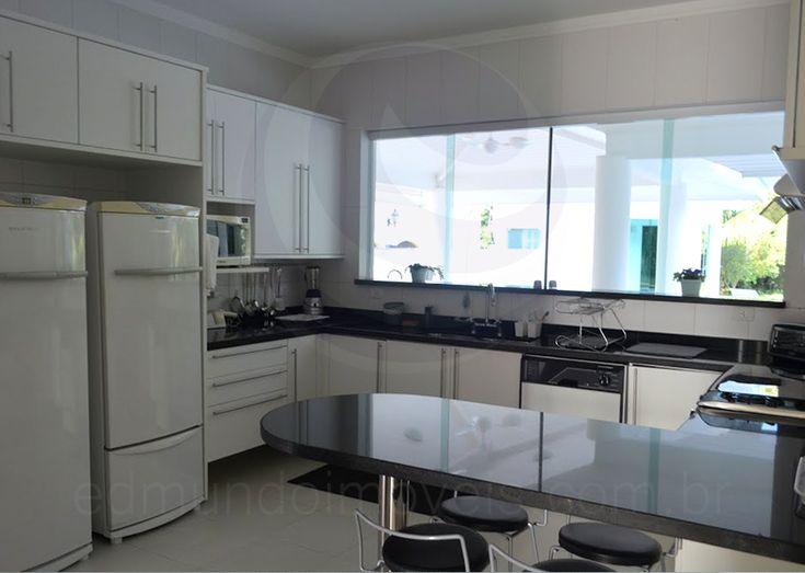 Uma enorme janela sobre a pia mantém o cômodo bem arejado e iluminado, além de proporcionar melhor integração com o espaço gourmet, localizado sob o alpendre, na área externa da residência.
