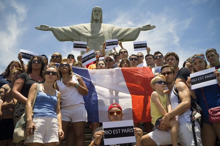 "People hold up a France national flag and signs that read ""Rio is Paris,"" during a demonstration in front of Christ the Redeemer statue, in Rio de Janeiro, Brazil."