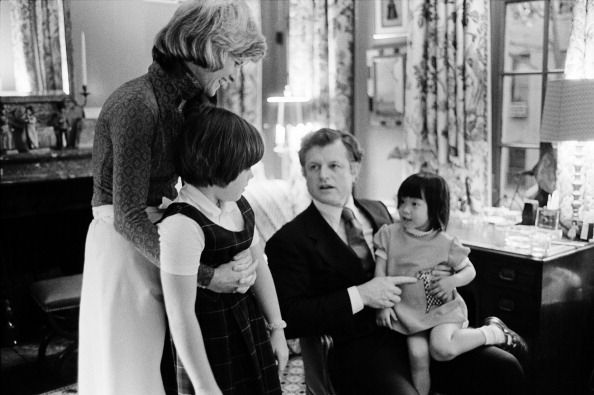 American politician US Senator Ted Kennedy (born Edward Kennedy, 1932 - 2009) visits his sister Jean Kennedy Smith and her daughters in their Upper West Side town house, New York, New York, 1976. Kennedy holds one of his nieces, Kym Smith, on his lap as the other Amanda Smith, looks on.