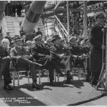 Black and white photograph of Captain Hustvedt giving speech at the commissioning ceremony of BB-55, April 9, 1941. Next to Broughton is Admiral Harold Stark, Chief of Naval Operations (behind Hustvedt)
