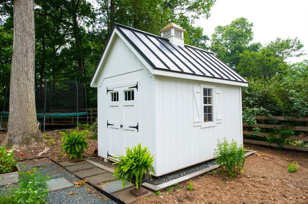 Farmhouse-style shed. A standing-seam metal roof, a mini cupola, shutters and carriage doors add up to a charming farmhouse-style look. Traditional Garage And Shed by Smithouse