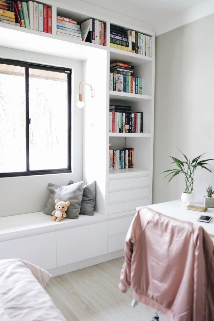 Estante branca de livros contornando a janela com lugar para sentar e ler com luz natural.  #bookshelf #windowseat #estantedelivro