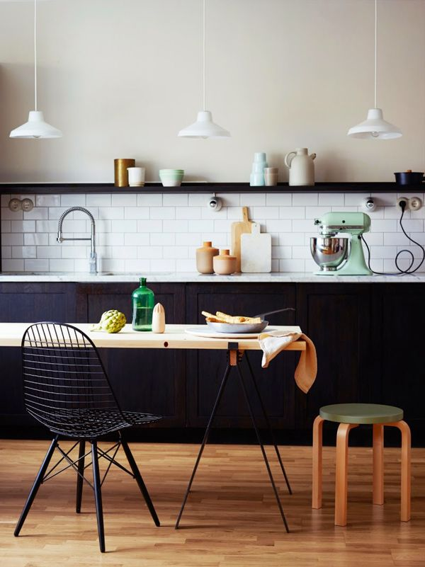 Black and white kitchen with minimal furniture and open shelving.