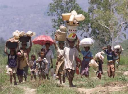 """East Timorese refugees carry their belongings as they cross the border back into their homeland near the town of Memo Tuesday. Thousands of East Timorese, who were forcibly deported to West Timor by pro-Jakarta authorities following a vote for East Timor's independence from Indonesia, trickled across the border after walking in intense heat for hours, with at least five people reported dead during the trek. (Jason Reed/Reuters)"""