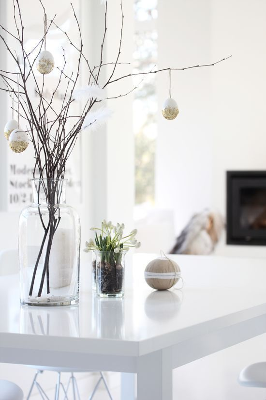 Easter Decoration, dining room table for the Holiday. Decorate with eggs, feathers and flowers with white Scandinavian interior.