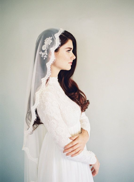 Uma noiva clássica com mantilha trabalhada em renda. Tradicional e lindo! Casamentos com forte presença das tradições de família combinam bem com estes detalhes.