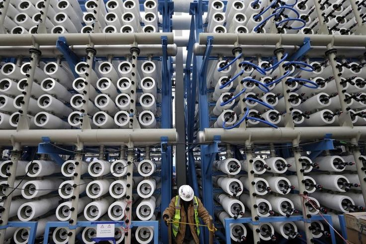 FILE - In this March 11, 2015, file photo, a worker climbs stairs among some of the 2,000 pressure vessels used to convert seawater into fresh water through reverse osmosis in the western hemisphere's largest desalination plant in Carlsbad, Calif. The Carlsbad Desalination Project, scheduled to start operations in late 2015, is expected to provide 50 million gallons of fresh drinking water a day. A plan to pump $1 billion of water spending into drought-stricken California cleared the…