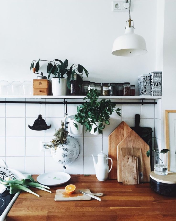 white square tile, white pendent, chopping boards stacked, open shelves, hanging bar