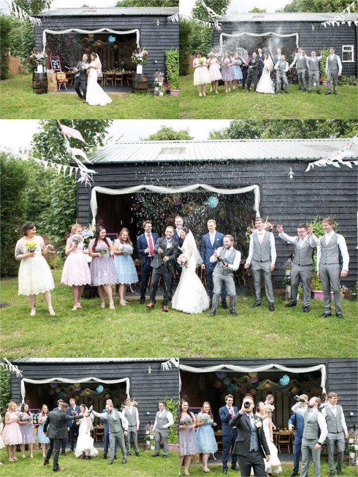 Bury St Edmunds documentary wedding photography. Bride and groom spraying champagne at rustic farm wedding