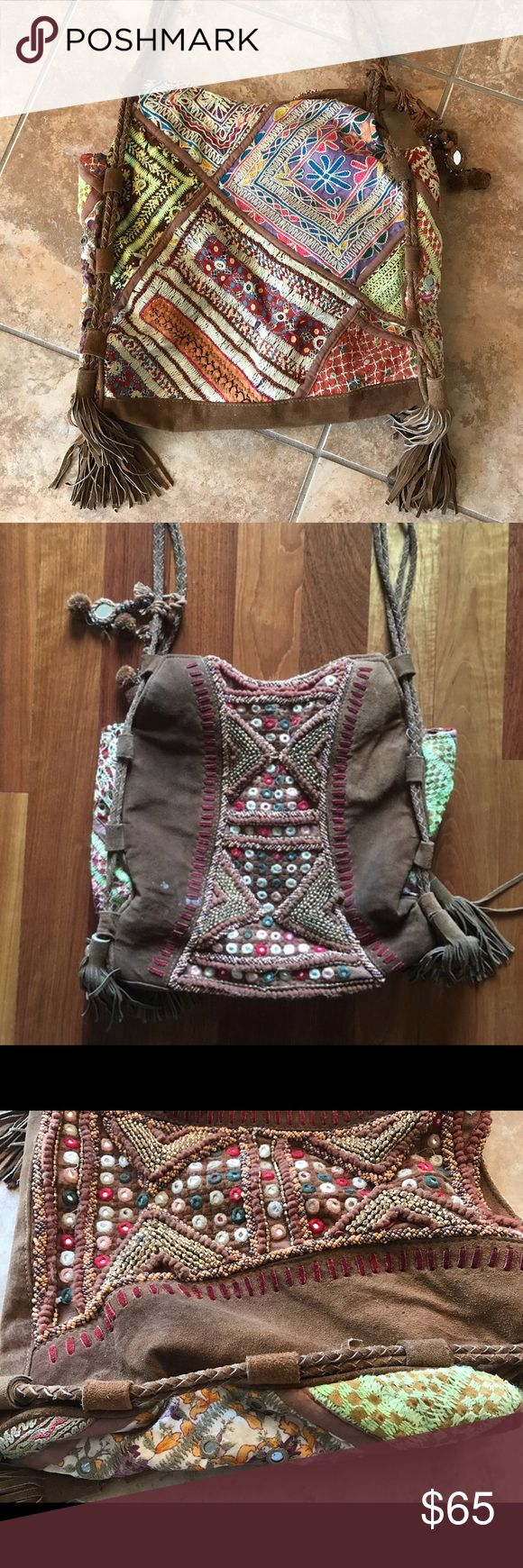 Free People Boho Embroidered Bag Free People Boho Embroidered Bag. So unique and beautiful! One side with gorgeous embellishments and bright colors and the other side with embellishments up the middle. Bright embroidery on the sides. I believe it is suede. Tassels on both sides and braided long straps. So many bells and whistles! 🙃 May be worn on one shoulder or even as a cross body. Inside with FP tag and pockets, looks to be a wax stain inside and outside (photos 2 and 4). Good condition…