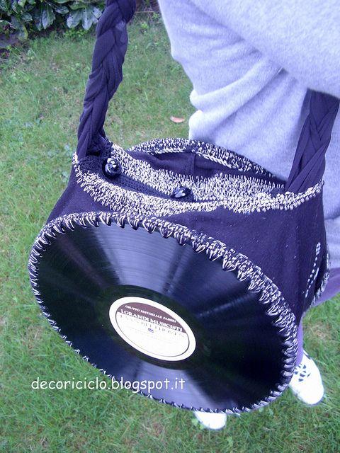 borsa fatta con 2 dischi in vinile 33 giri, uniti da stoffa ricavata da leggins rotti, assemblata con cotone mélange nero e beige all'uncinetto, con manico a treccia ricavato da una T-shirt smessa
