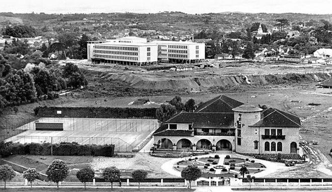 """Vista tirada do alto do Edifício Tamoio, onde vemos (em primeiro plano) a sede do Círculo Militar. Vindo a seguir o conjunto do Colégio Estadual do Paraná, ainda em construção. Destaque da terraplenagem executada no terreno, antiga elevação onde existia a chácara de """"Nhá"""" Laura Borges. A paisagem se dirige ao horizonte, em direção ao espaço em que seria instalado o futuro Centro Cívico. A fotografia foi feita no ano de 1947."""