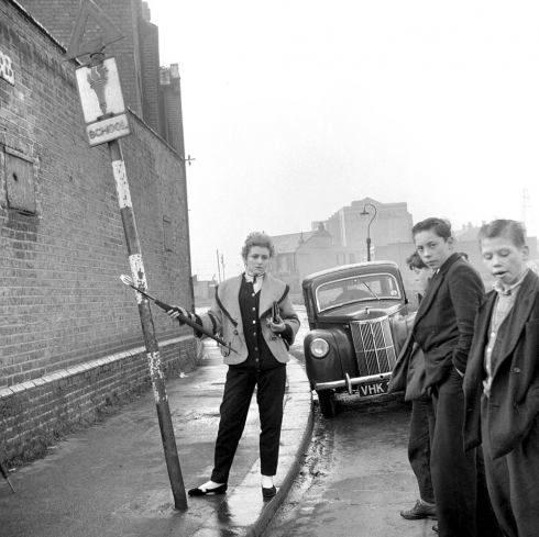 In 1955, the fledgling photographer created a series called The Last of the Teddy Girls, which featured photographs taken against the war-torn backdrop of London's East End. The images are one of the first reportage series to be made of British youth culture, presenting pictures of working class girls in Neo-Edwardian dress—a fascinating counterpoint to their drape-coated and drainpipe-wearing male counterparts the Teddy Boy. T