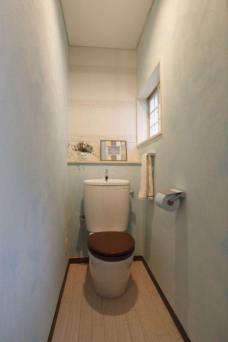 トイレのリフォーム。壁は淡いブルーとホワイトの水性ペイントで仕上げました。やわらかなグラデーションがサニタリー空間に落ち着いた雰囲気を与えます。正面の壁は匂いの吸着や湿度の調整機能を持ったエコカラットをパターン貼りにしてフォーカルポイントに。あたたかみのある木製便座もアクセントになっています。背面の小さな棚には癒やしの小物を飾って。家族やお客様の目を楽しませてくれます。