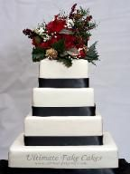 4 tier white wedding cake with black ribbon and fresh flower topper