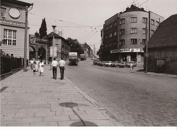 Ulice u Prazdroje na snímku z roku 1986. V následujících letech byla rozšířena do současné podoby. Na budově pivovaru nemohl chybět transparent upozorňující na XVII. sjezd KSČ a vůdčí roli strany...