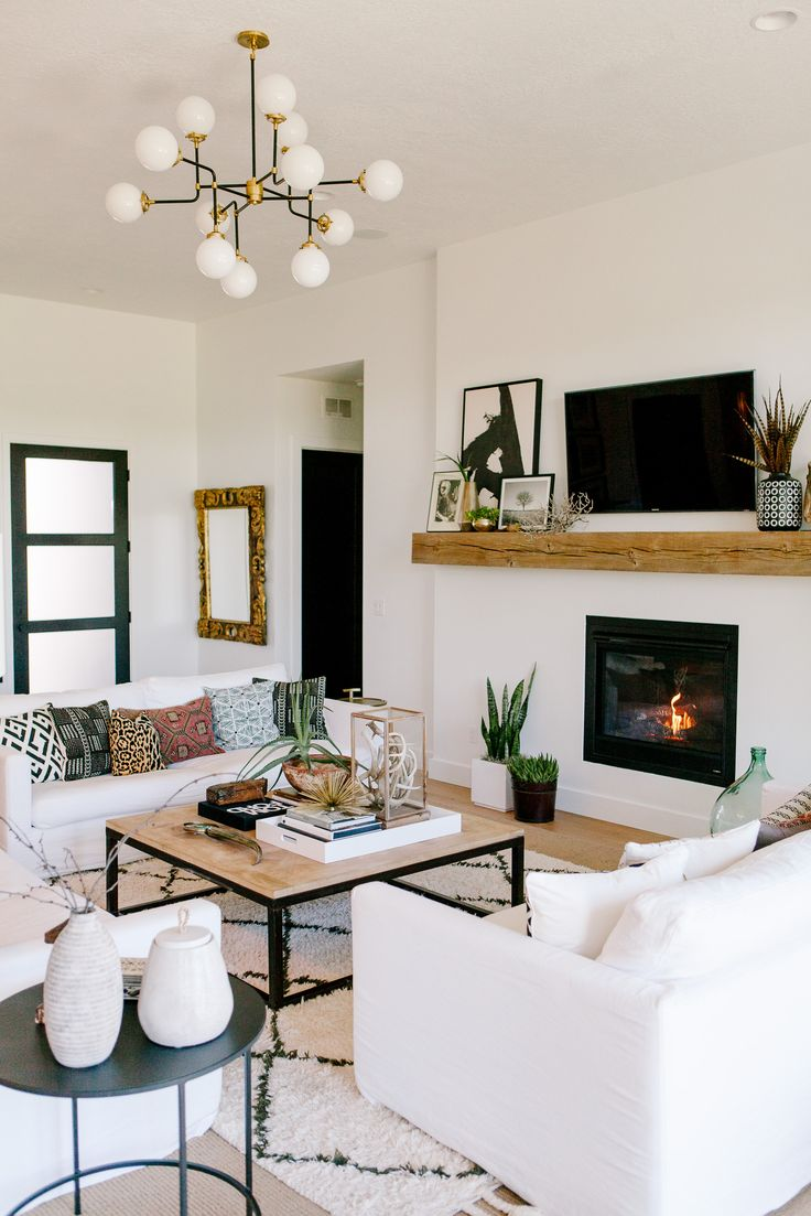 black and white living room, white sofas, mud cloth pillows, turkish pillows, old timber mantle, large coffee table, modern chandelier, lynsdesignstyle