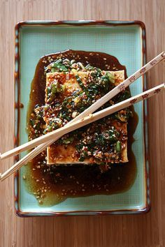 Warm Tofu with Spicy Garlic Sauce | • 1 (14- to 18-oz) package firm tofu • 1 tsp chopped garlic • ¼ cup chopped scallion • 2 tsp sesame seeds, toasted & crushed with side of a heavy knife • 3 TB soy sauce • 1 TB Asian sesame oil • 1 tsp coarse Korean hot red-pepper flakes (crushed red pepper flakes) • 1/2 tsp sugar