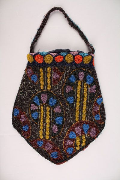 Date Made: 1910  Description:  Purse; beaded, multi-colored abstract floral design with red and gold circle motifs at top. Seed beads completely cover black net lace. Floral design in blue, lavender, and gold on a black and brown ground. Alternating red and gold circles on a navy blue ground border top. Circles in blue and lavender are incomplete as they are folded over top edge. Handle is fully beaded as well. Purse is lined in navy blue silk. Two small snaps secure closure.