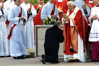 What Is the Sacrament of Communion in the Catholic Church?: Pope Benedict XVI gives Polish President Lech Kaczynski (kneeling) Holy Communion during Mass at Pilsudski Square May 26, 2006, in Warsaw, Poland.