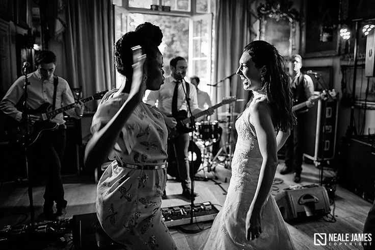 A bride laughs while her friend energetically dances to their wedding band. Image taken using only natural light via nealejames.com