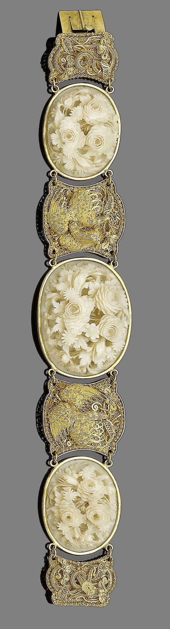 A late 19th century gold and ivory bracelet Set with three oval ivory plaques, each finely carved in high relief depicting floral bouquets, with graduated gold filigree spacers depicting phoenixes and serpents, Chinese maker's mark, retailer's mark W.W, damage to one filigree plaque, length 18.2cm, later fitted ivory case