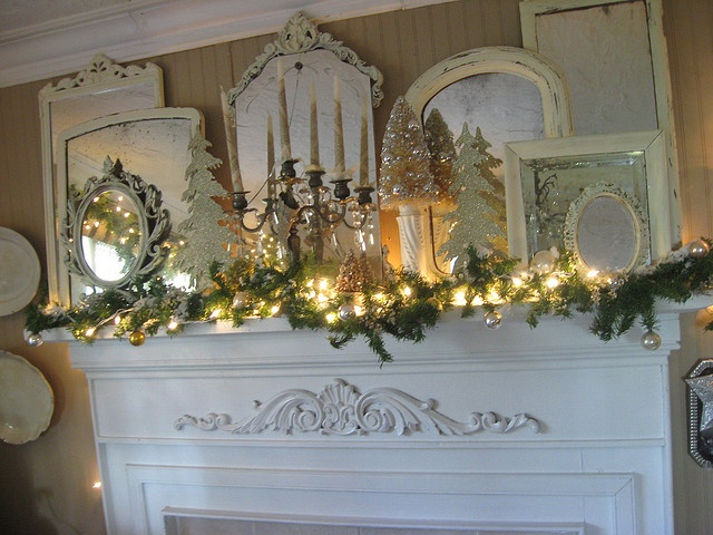 gorgeous mantel - love the vintage mirrors reflecting the lights and candles (by Tin Rabbit)