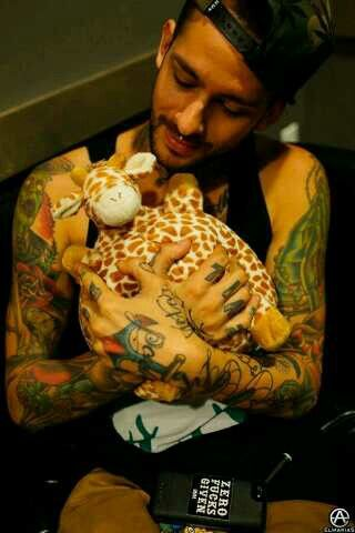 Pierce the Veil Challenge Day 5: Favorite picture of Mike?- This. I mean it is literally everything Mike in one picture. Badass tatoos and piercings (and phone case), but he's also smiling and holding a stuffed giraffe! What's not to love?
