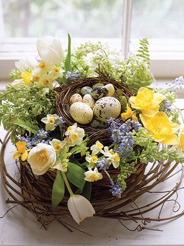 Flowers and eggs (real and artificial) rest in a bird's nest filled with wet florist's foam. Get the complete instructions. #Easter