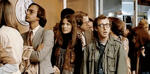 "A still from ANNIE HALL, as Annie and Alvy wait to get into a movie. Cognoscenti know a man who thinks he's a film maven starts talking pompously about Marshall McLuhan, causing Alvy to roll his eyes. Lo and behold, McLuhan shows up and chews out the jerk, telling him, ""You know nothing of my work."" Ah, if only life really worked this way!"