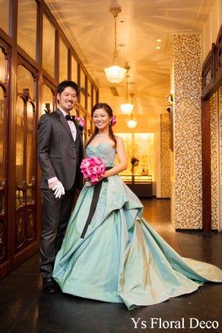 メゾンポールボキューズ挙式の新婦さんへ 水色のドレスに鮮やかなピンクのブーケとヘッドドレス