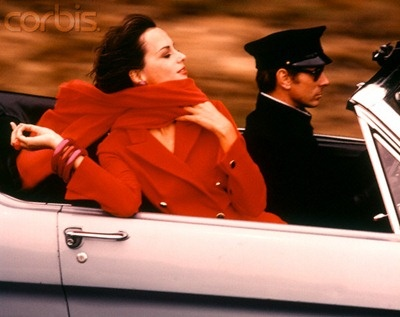 """""""When in doubt, wear red."""" Bill Blass Stylish Woman In Red Dress And Scarf Riding In Convertible Sports Car Driven By Chauffeur, 1970s."""