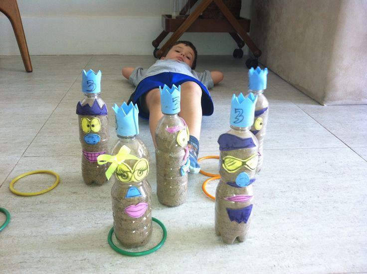 Jogo de argolas em garrafas de plástico cheias de areia e decoração de monstrinhos em EVA