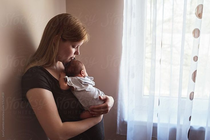 Portrait of a new mother snuggling with her baby by Lea Csontos for Stocksy United
