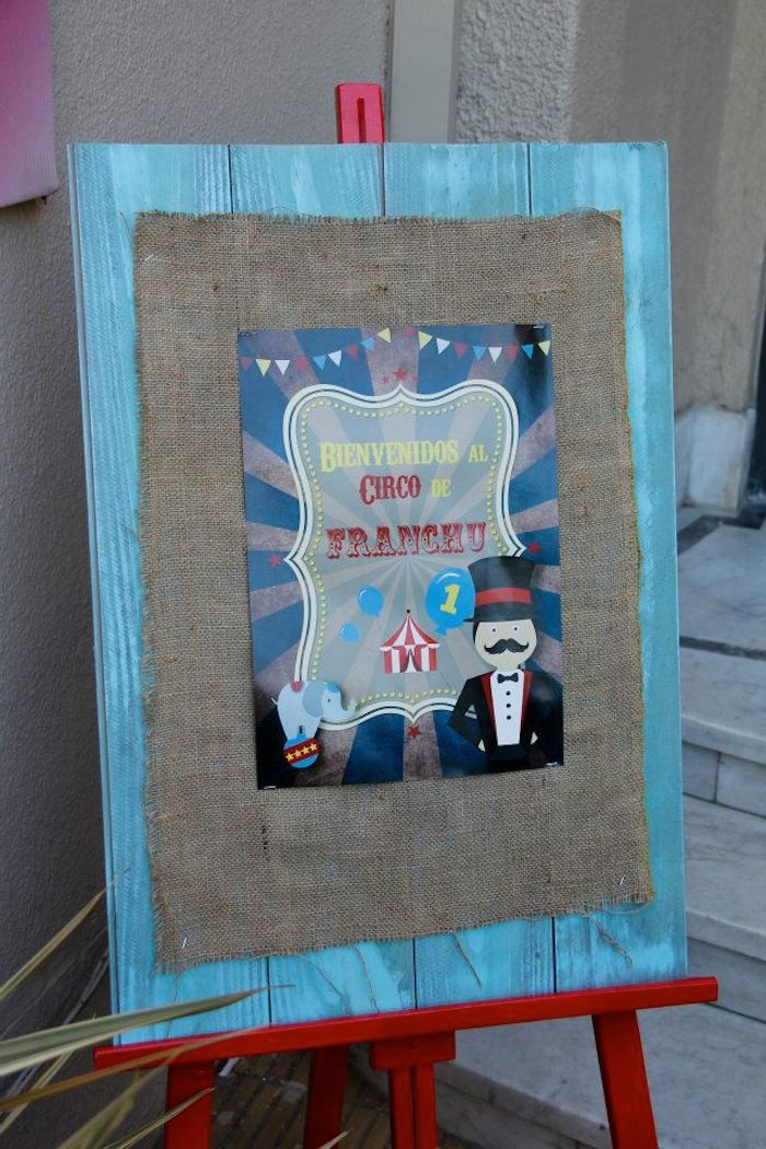 """DECORATION: """"Welcome to the Circus"""" Sign on burlap, on a blue wood board, on a red easel"""