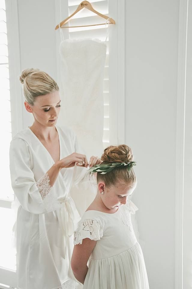 Bride in a lace ivory robe with her flower girl. Wearing a flower crown