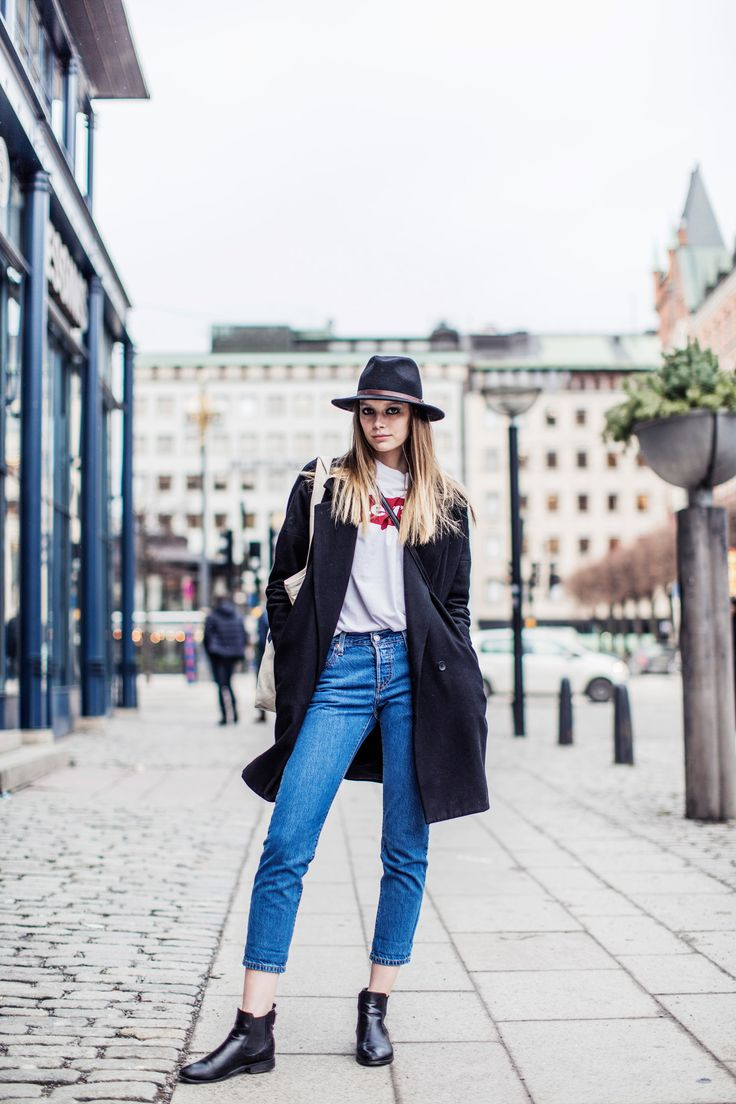 Seen in Stockholm. Pair your bright blue jeans with a Levi's graphic t-shirt, felt flat-brimmed hat, black leather booties and wool coat.