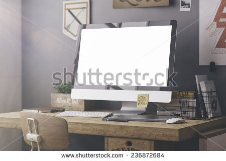 Stylish workspace with computer and posters on home or studio - stock photo