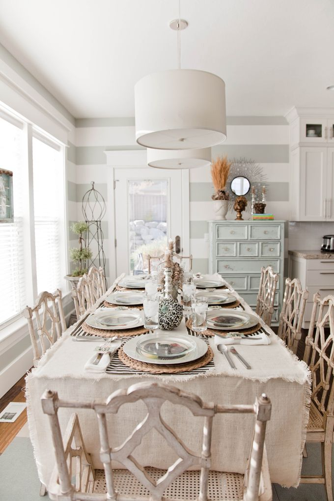 a twist on coastal style, love the grey stripe & the table decorating dressing, the chairs wouldn't go amiss either
