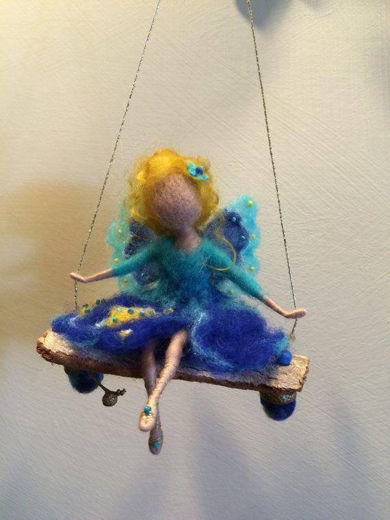 Die kleine Fee reitet auf einer Schaukel. Sie trägt ein helles türkises blaues Kleid mit gelben Blüten und mit Perlen verziert. Die Flügel haben die gleiche Farbe.  Die Schaukel ist mit Perlen und Eicheln aus der Wolle geschmückt.  Die Höhe der gesamten Komposition ist etwa 13(33 cm), die Höhe der Fee (sitzend) beträgt ca. 4,8 (12 cm).