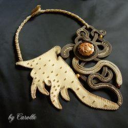 Naszyjnik inspirowany tatuażami tribal. Kompozycja sznureczków soutache została połączona ze skórą ekologiczną w kolorze ciepłego beżu i zwieńczona haftem koralikami Preciosa w kolorze złotym. Ramiona i zapięcie naszyjnika wyplecione metodą beading.