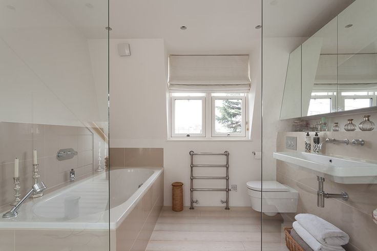 Creative ways to maximise space in a loft conversion. We were able to include an en-suite in this master bedroom by using glass walls to make the space feel as expansive as possible.