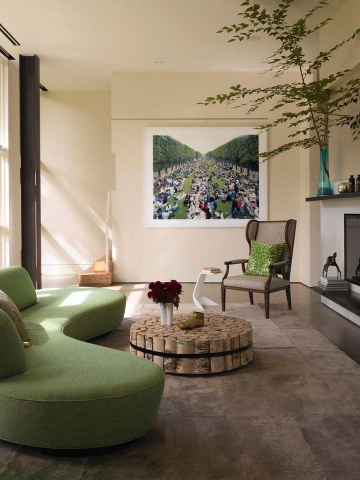 canapé demi lune vert et élégant, table basse en bois de bouleau et tapis marron dans le salon