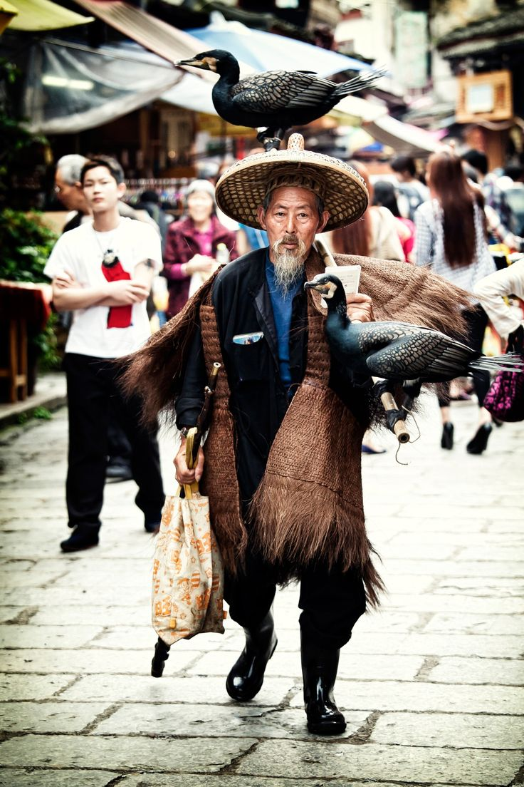 Cormorant man, Yangshuo, China. Years ago this man used his bird to catch fish. A string tied around the birds neck would prvent it from swallowing the fish.