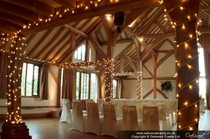 Pillars wound with fairy lights in the music room for a wedding at Cain Manor