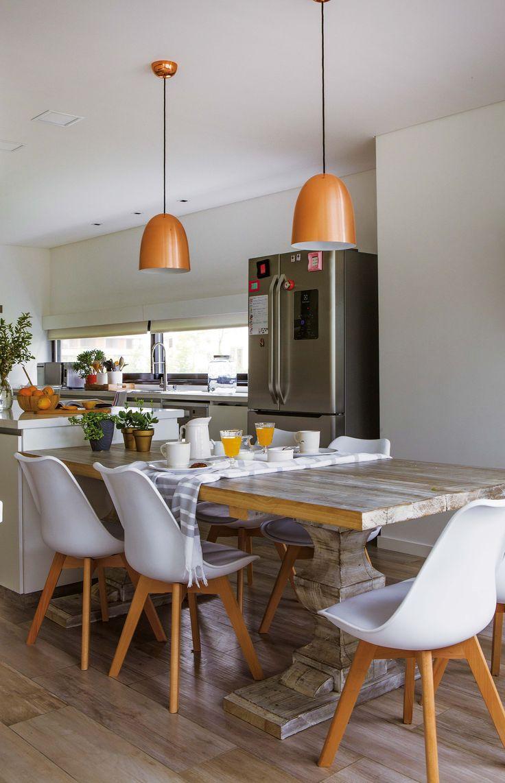 Cocina entre rústica y moderna en una casa en un country, con mesa de madera estacionada con patas copa, sillas tipo Eames y las lámparas colgantes de cobre.