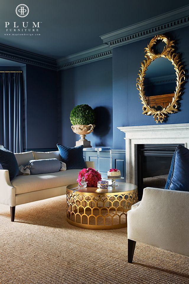 Two neutral sofas facing each other in front of a fireplace is a common arrangement. The deep dark blue walls are anything but. Add gold accessories, a dynamite coffee table and blue throw pillows and it's magic...