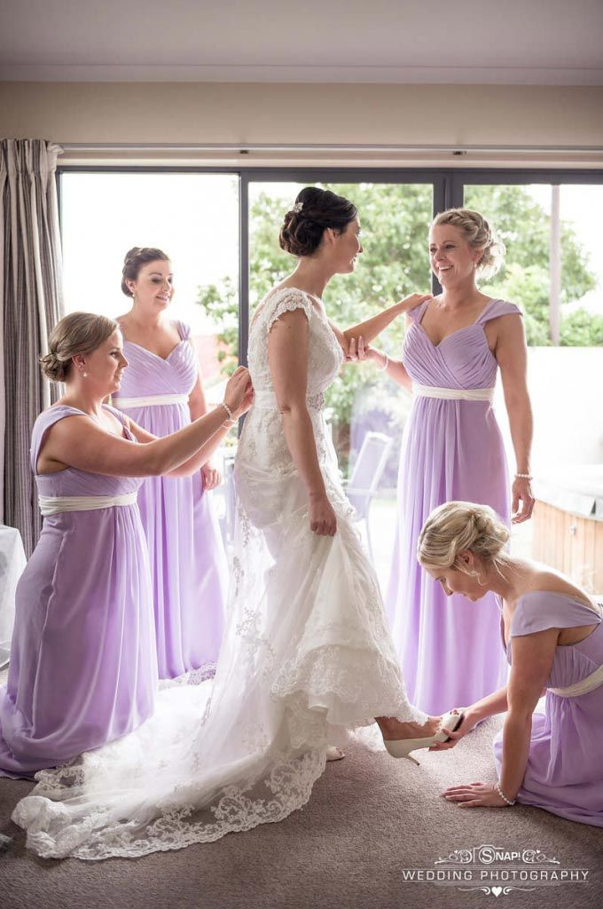 The bridesmaids help the gorgeous bride get ready. Check out other wedding photography by Anthony Turnham at www.snapweddingphotography.co.nz