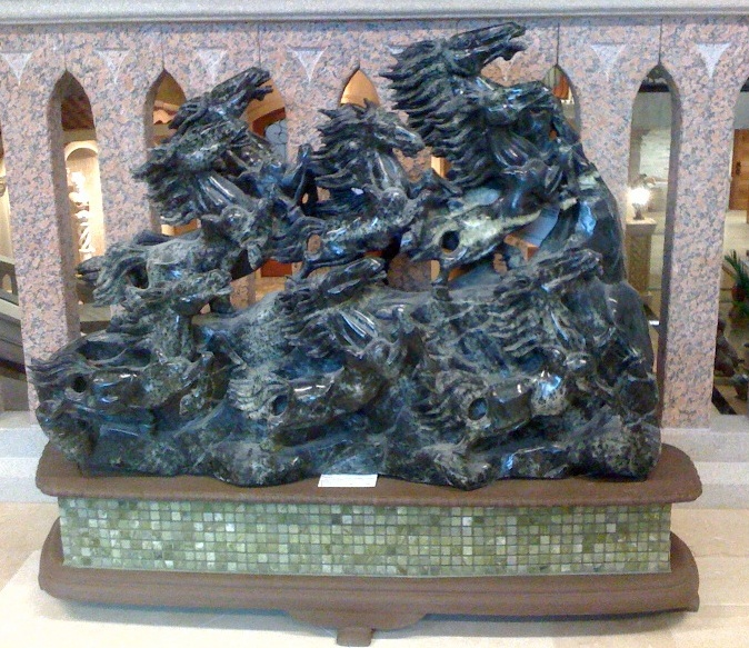 This breathtaking Dark Green Jade carving from Carved Stone Creations features a majestic herd of horses galloping across rocky terrain. The horses gradually increase in size from left to right creating a strong diagonal that catches your eye. The carving is mounted to an attractive wood stand that features a band of complimenting green jade tile mosaic. $15,500  Click on the image to see it in our online store.