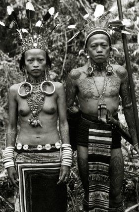 Borneo | Dayak couple in traditional dress and tattoos, c.1920 | ©Prismatic Pictures